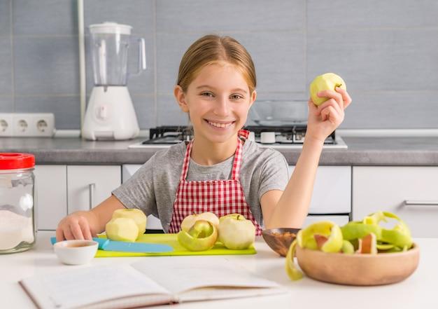 Bambina allegra con mela sbucciata in mano