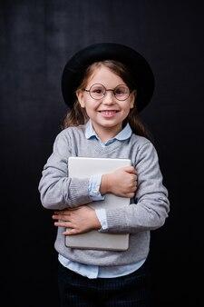 Bambina allegra con il sorriso a trentadue denti che tiene compressa digitale dal petto mentre levandosi in piedi in isolamento contro lo spazio nero