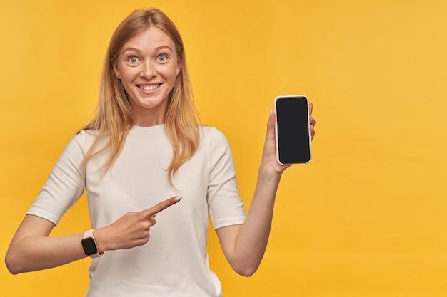 Giovane donna bionda adorabile allegra con le lentiggini in maglietta bianca che tiene smartphone a schermo vuoto e che punta su di esso sul muro giallo