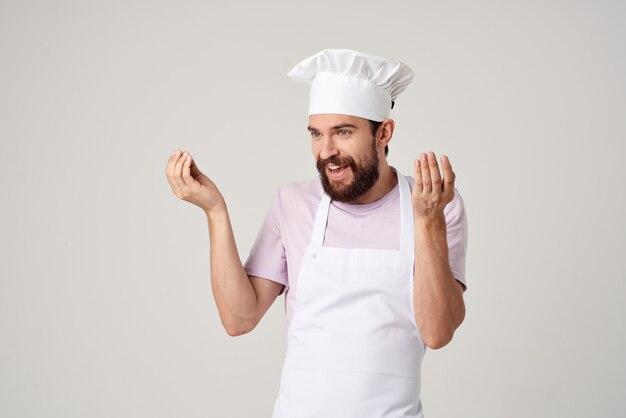 Cuoco unico maschio allegro nei gesti uniformi con il suo ristorante gourmet delle mani