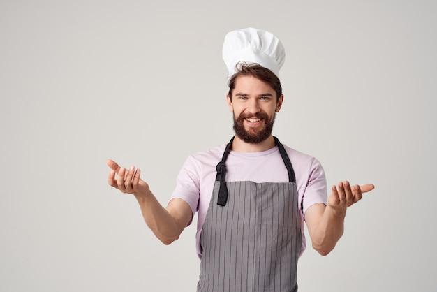 Cuoco unico maschio allegro in cucina professionale di lavoro uniforme