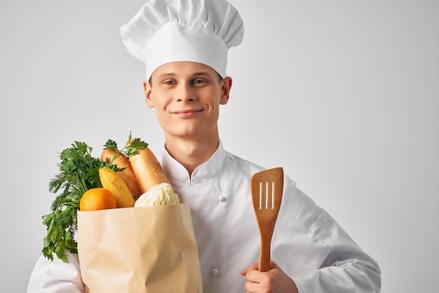 Chef maschio allegro con un pacchetto di prodotti alimentari sani che forniscono servizi di cucina