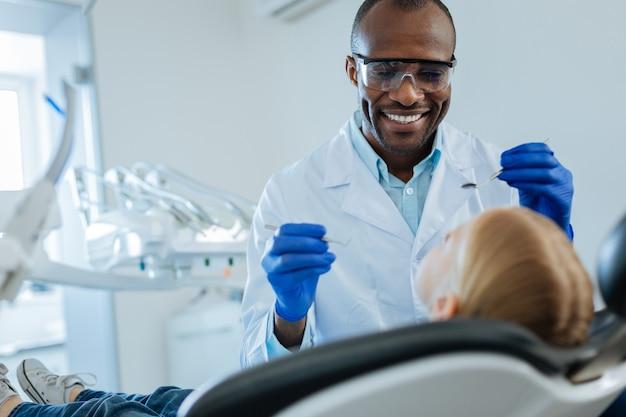 Dentista maschio allegro che tiene uno specchio della bocca e una sonda dentale e sorride al suo piccolo paziente mentre effettua l'esame della cavità orale