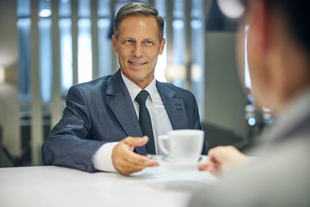 Il maschio allegro in abito elegante e cravatta sta ordinando una tazza di tè dalla barista al ristorante