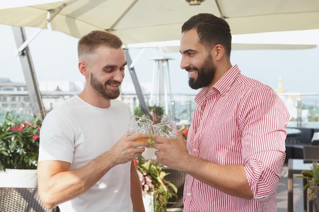 Allegri amici maschi tintinnano bicchieri, bevendo al bar sul tetto