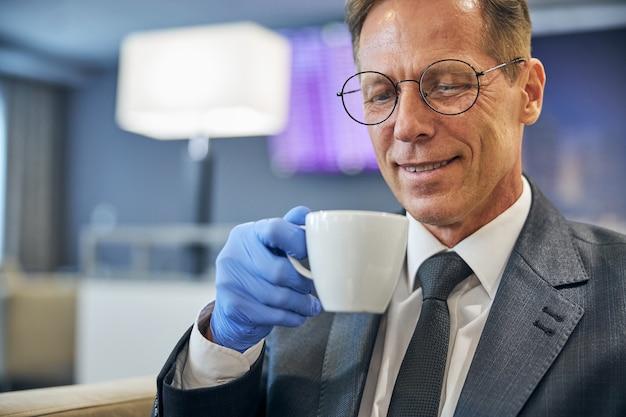 Un uomo allegro con occhiali e guanti in lattice si sta godendo il caffè mentre è seduto nella lounge dell'aeroporto