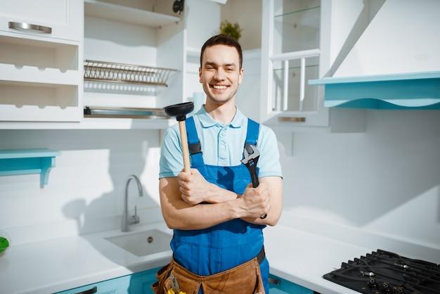 L'idraulico maschio allegro in uniforme tiene la chiave inglese e lo stantuffo in cucina. tuttofare con lavello per la riparazione della borsa degli attrezzi, servizio di attrezzature sanitarie a casa