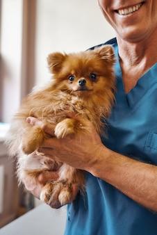 Allegro veterinario maschio che tiene un simpatico cagnolino con gli occhi spaventati mentre si trova in una clinica veterinaria veterinary