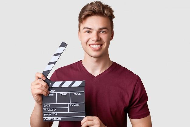 Il maschio allegro con l'ampio sorriso, porta la maglietta casuale, tiene il ciac, ha partecipato al nuovo film della creazione, isolato su bianco. per il film. produzione e realizzazione di film