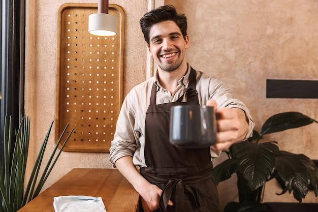 Uomo allegro barista che indossa un grembiule in piedi al bar, mostrando la tazza di caffè