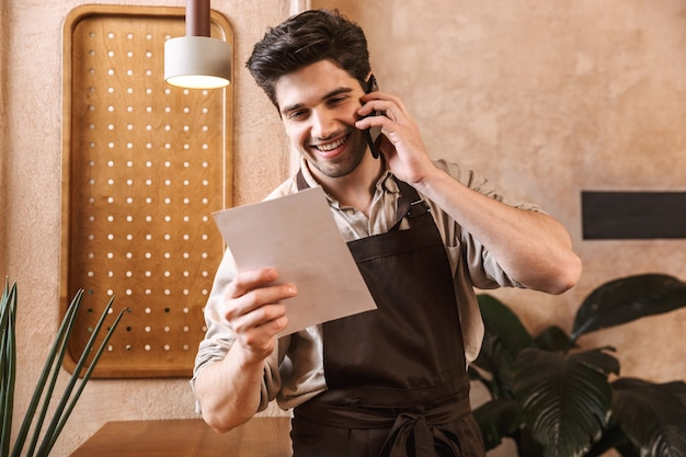 Barista uomo allegro che indossa un grembiule in piedi al bar, prendendo un ordine con il telefono cellulare