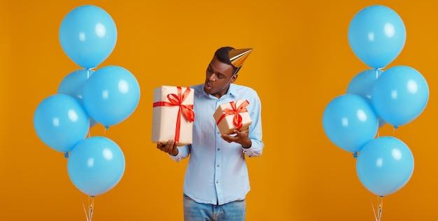 Uomo allegro in berretto che tiene due scatole regalo con nastri rossi, sfondo giallo. la persona di sesso maschile sorridente ha ricevuto una sorpresa, un evento o una festa di compleanno, una decorazione di palloncini