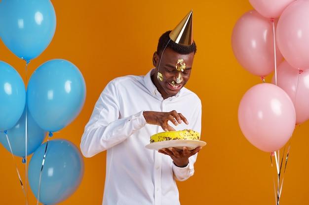 Uomo allegro in berretto con torta di compleanno degustazione faccia spalmata. la persona di sesso maschile sorridente ha ricevuto una sorpresa, la celebrazione dell'evento, la decorazione di palloncini