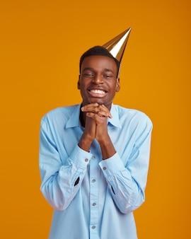 Uomo allegro in berretto, sfondo giallo. la persona di sesso maschile sorridente ha ricevuto una sorpresa, un evento o una festa di compleanno, in attesa di una sorpresa