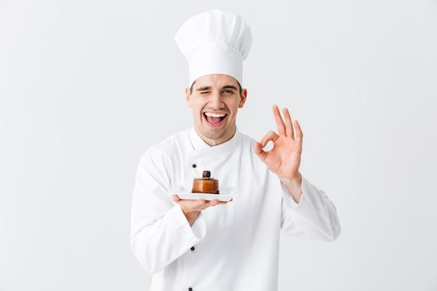 Cuoco unico allegro dell'uomo che indossa l'uniforme che mostra la pasticceria su un piatto isolato sopra la parete bianca
