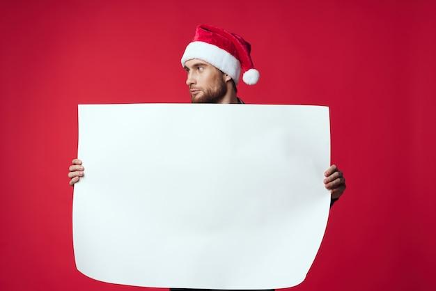 Uomo allegro in un poster di mockup bianco di natale sfondo rosso