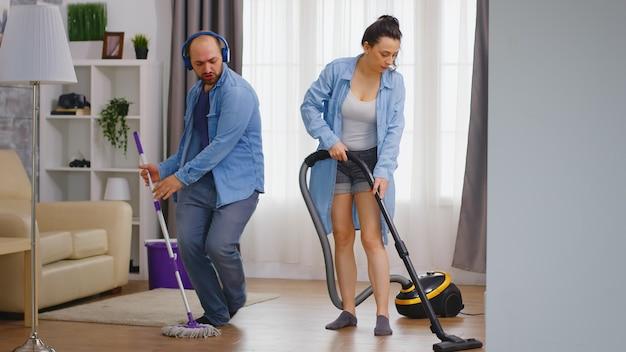 Uomo allegro che balla mentre pulisce la casa insieme a sua moglie
