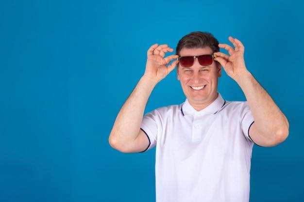 Un uomo allegro con gli occhiali scuri e una camicia bianca sorride su sfondo blu