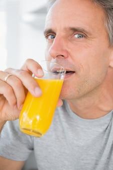 Uomo allegro che beve il succo di arancia in cucina