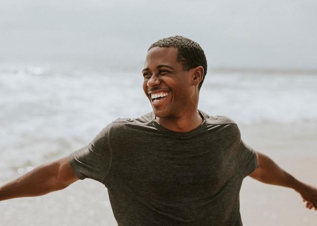 Uomo allegro che si gode sulla spiaggia