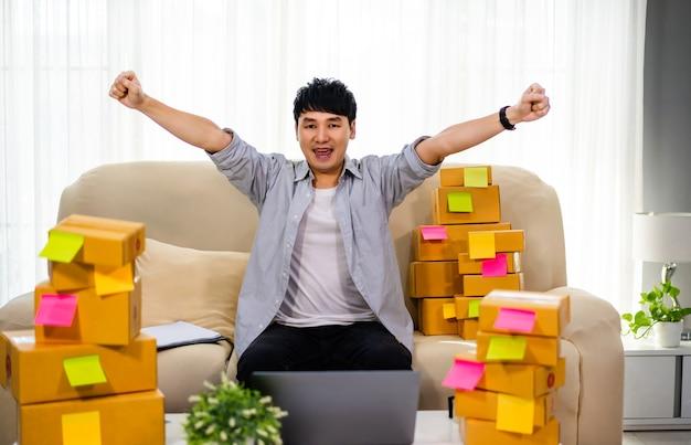 Imprenditore uomo allegro che lavora con il computer portatile e successo nella vendita di prodotti online in ufficio a casa
