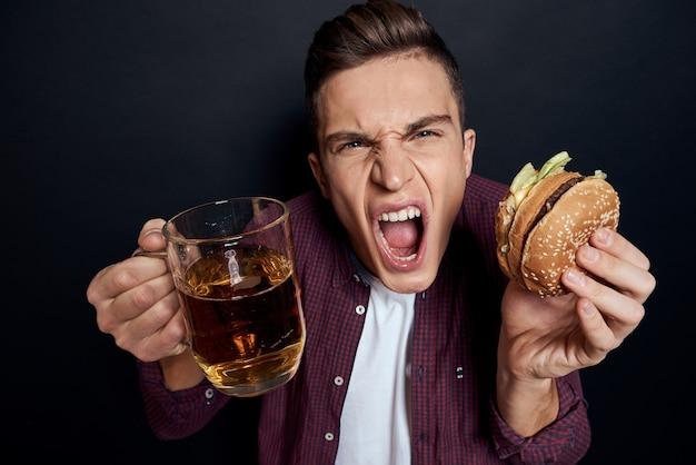 Uomo allegro fast food assunzione di cibo cibo sfondo nero ristorante. foto di alta qualità