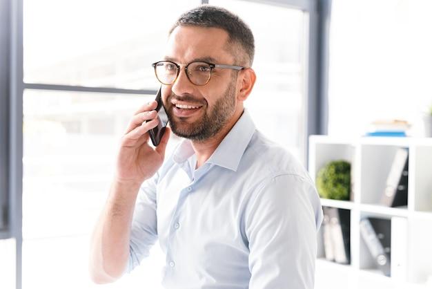 Uomo allegro in abbigliamento formale e occhiali da vista parlando al telefono cellulare nero di affari, mentre si lavora in ufficio