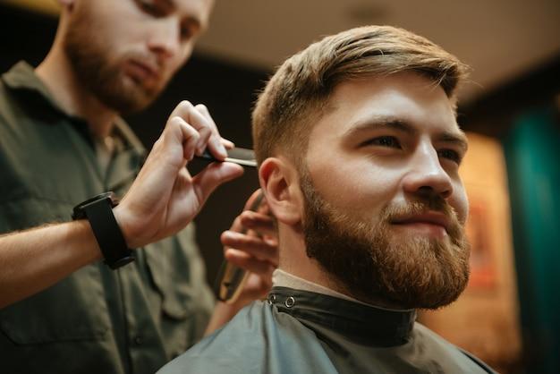 Uomo allegro che si fa tagliare i capelli dal parrucchiere con il rasoio mentre è seduto in poltrona. guardare oltre.