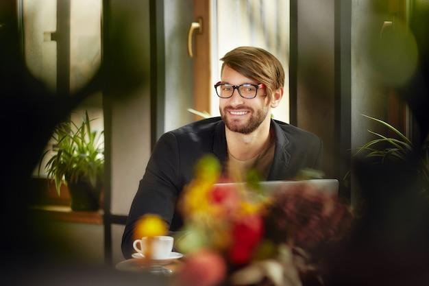 Uomo allegro con gli occhiali al computer portatile