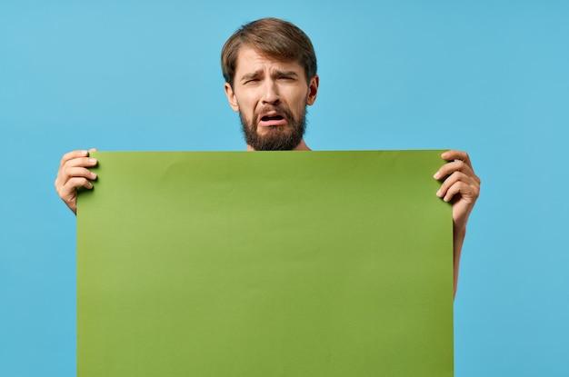 Striscione verde uomo allegro in mano foglio bianco sfondo blu