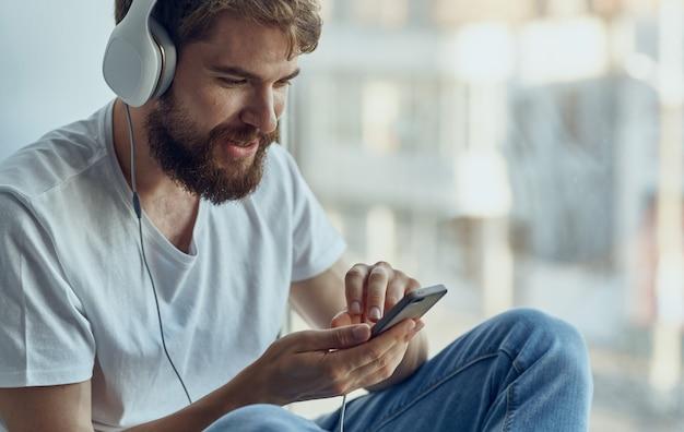 L'uomo allegro in cuffie ascolta la musica sul davanzale della finestra. foto di alta qualità