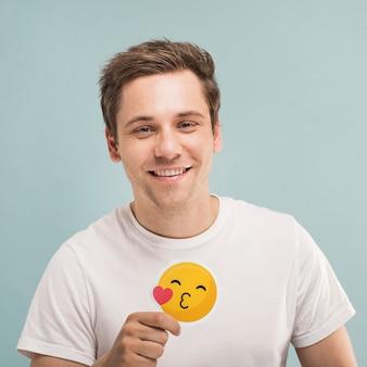 Uomo allegro che tiene un'icona di bacio che soffia