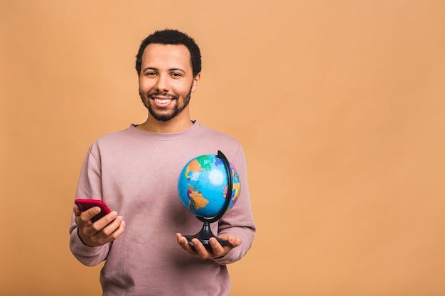Uomo allegro che tiene il globo con amore e cura isolato sul beige