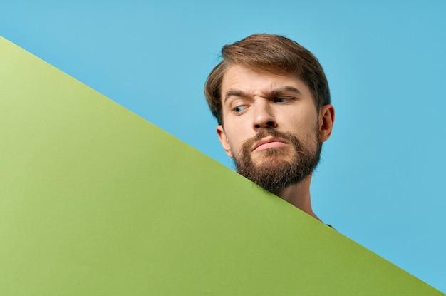 Uomo allegro che tiene il fondo blu di sconto del manifesto del mockup verde