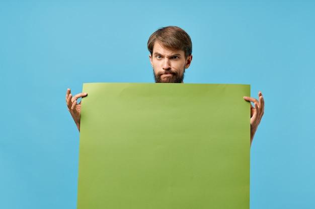 Uomo allegro che tiene studio copyspace di sconto poster mockup verde