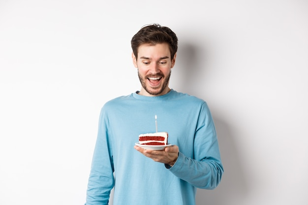 Uomo allegro che guarda felice la torta di compleanno, festeggia il compleanno, in piedi su sfondo bianco.