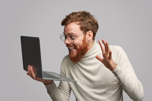 Uomo allegro che esamina il computer portatile con il premio