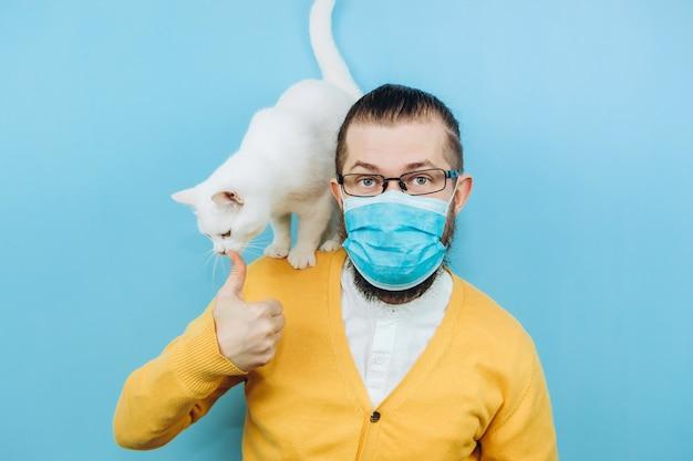 Un uomo allegro in una mascherina medica con un gatto bianco sulla sua spalla. pandemic covid 2019. animale domestico.