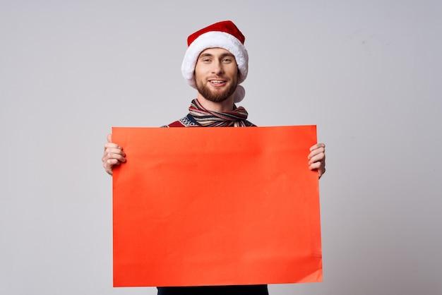 Uomo allegro in vestiti di capodanno che tiene uno sfondo isolato vacanza banner