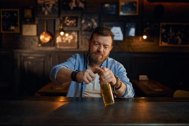 L'uomo allegro apre la bottiglia di birra al bancone del bar. una persona di sesso maschile che riposa in un pub, emozioni umane, attività ricreative, vita notturna