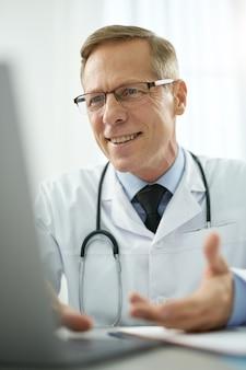 Medico allegro che parla con il paziente online e sorride mentre è seduto al tavolo con il taccuino