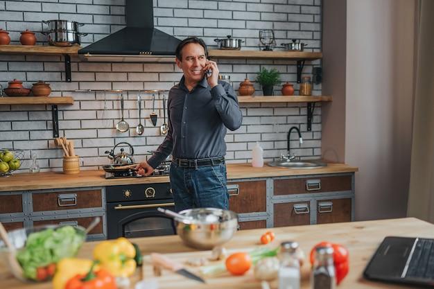 Supporto allegro dell'uomo alla stufa e conversazione sul telefono in cucina. si guarda indietro e sorride. computer portatile e verdure coloful e spezie sulla tavola.