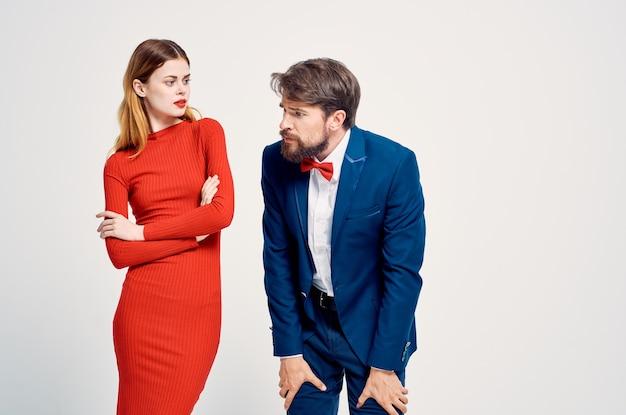Uomo allegro in abito accanto a una donna con un vestito rosso conoscente