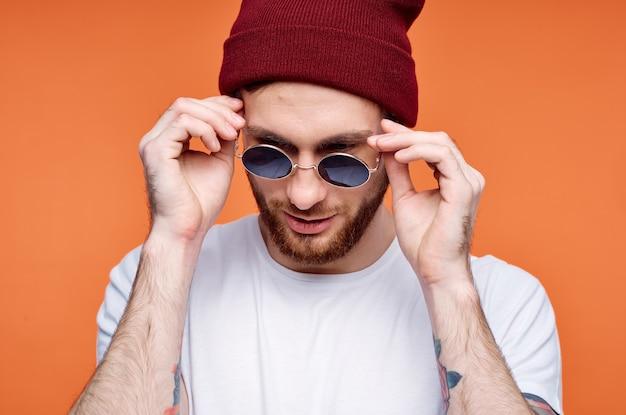 Uomo allegro in occhiali da sole che tiene uno sfondo di fiori arancioni
