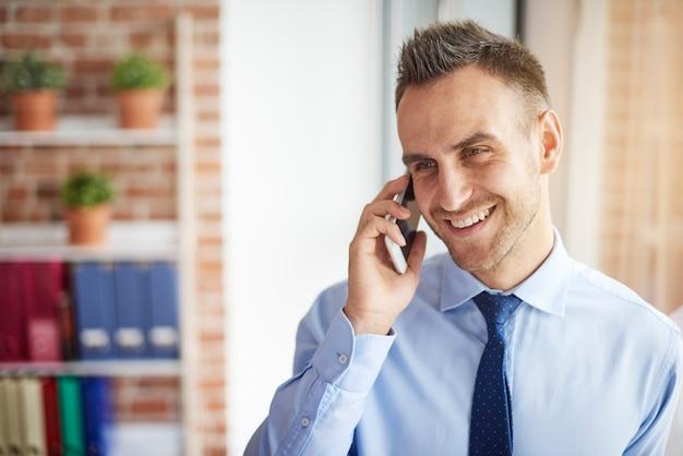 Uomo allegro che parla al telefono