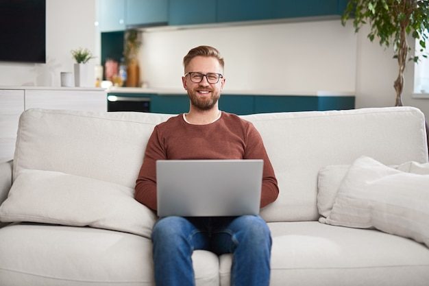 Uomo allegro che usa il laptop in soggiorno