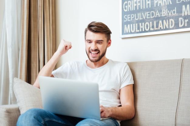 Uomo allegro che guarda la partita sul computer portatile a casa