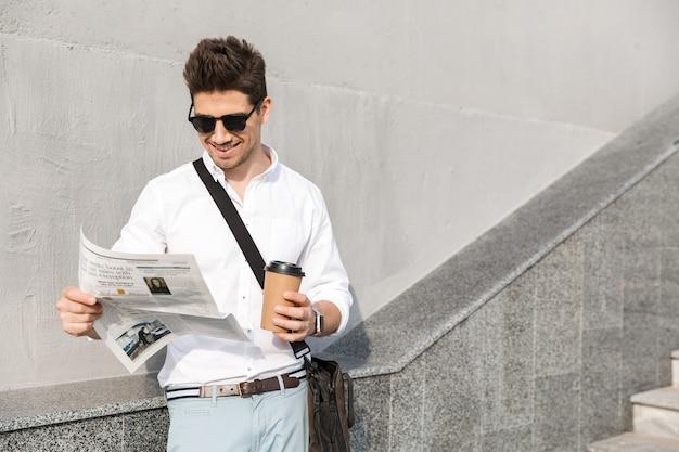 Uomo allegro che indossa occhiali da sole, beve caffè da asporto e legge il giornale, stando in piedi lungo il muro all'aperto