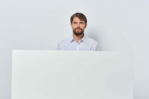 Bandiera bianca dell'uomo allegro a disposizione fondo bianco di presentazione del foglio bianco
