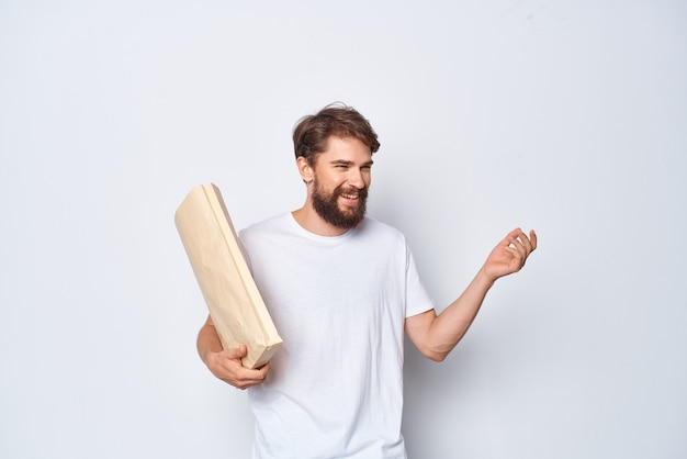 Uomo allegro in maglietta bianca con sfondo chiaro di imballaggio del sacchetto di carta